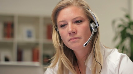 Female telephone customer service operator, happy, dolly shot