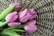 Beautiful bouquet of purple tulips, on grey wicker background