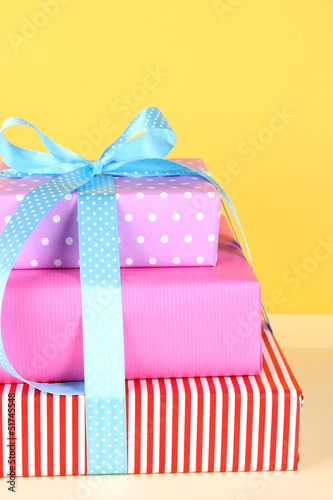 Gift box tied with a ribbon on a colored background