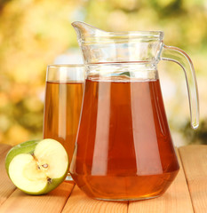 Full glass and jug of apple juice and apples