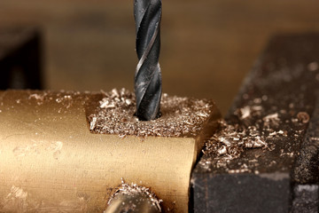 Drilling hole into metal, on wooden background