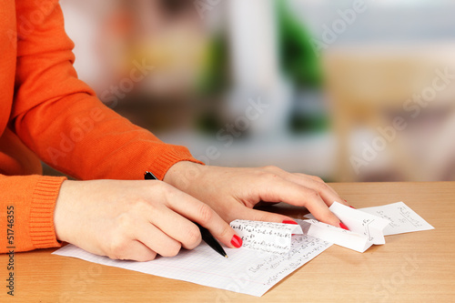 Write off exam on wooden table on room background