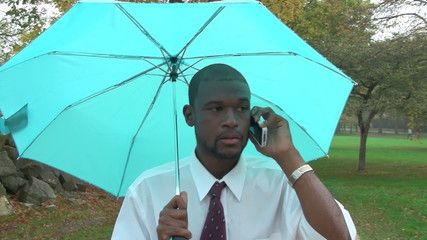 Business man on phone, walking under umbrella