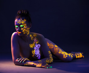 Attractive naked girl with UV makeup in studio