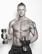 Sexy guy is holding dumbbells