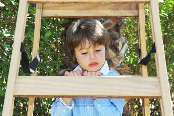 The boy climbed up a wooden sliding ladder