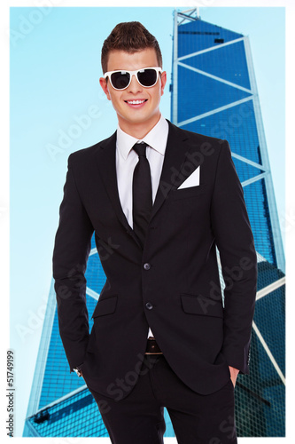 Young and stylish businessman in front of skyscraper