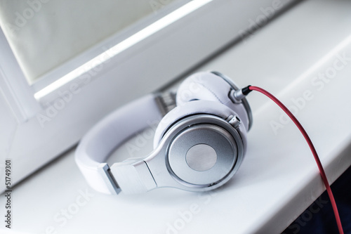 White headphones with red wire on the sill