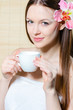 Portrait of a beautiful girl with flower in hair and cup