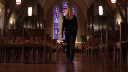 Woman entering church and sitting in pew, dolly shot