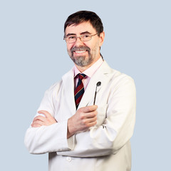 Portrait of happy middle-aged dentist on a pale background, wear