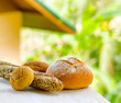 Fresh bread on white wooden table on rural landscape background