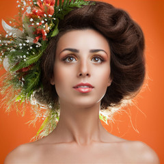 A beautiful girl with flowers on her head on an orange backgroun