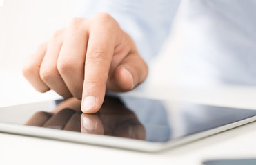 Close up of male hand using digital tablet