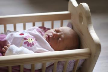 Baby in Puppenwiege schlafend