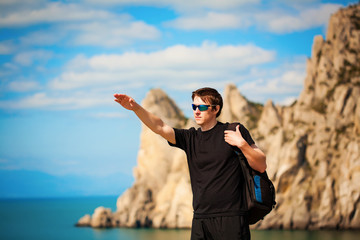 tourist is pointing the way from the rocks top