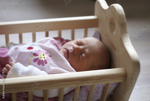 canvas print picture Baby in Puppenwiege schlafend