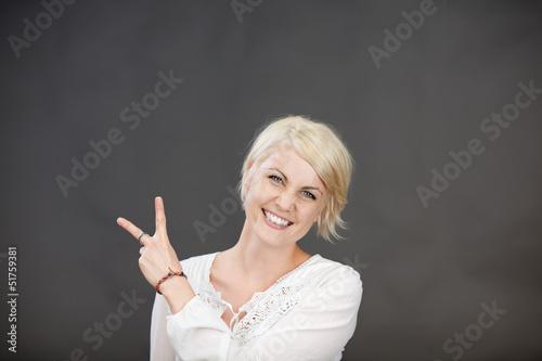 lachende blonde frau zeigt zwei finger