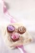 drei pralinen in cupcake form, rosa, lila und braun