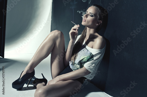 Fashion photo of sexy woman smoking a cigarette © kiuikson