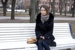 Beautiful young city woman sits on a bench