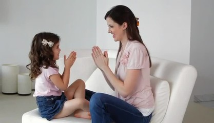 Caucasian mother and daughter clapping hands