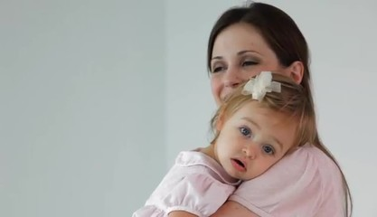 Caucasian mother holding daughter