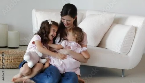 Caucasian mother hugging her daughters