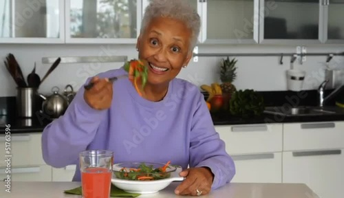 Senior African American woman eating salad