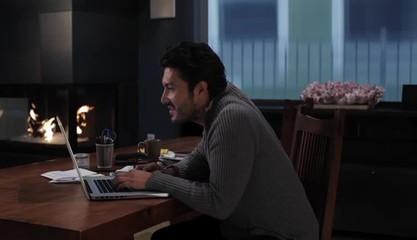 Hispanic man at laptop reading, cheering and walking away