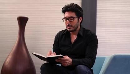 Hispanic man in creative space drawing in sketchbook