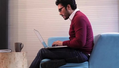 Hispanic man in creative space typing on laptop