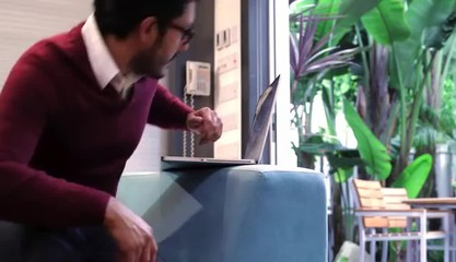 Hispanic man in indoor/outdoor creative space typing on laptop