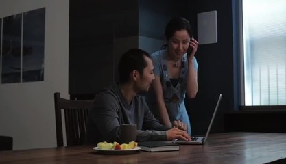 Japanese couple at home searching laptop and using cell phone