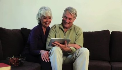 Senior Caucasian couple at home sharing digital tablet