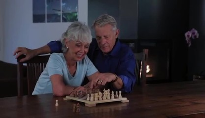 Senior Caucasian couple at home playing chess