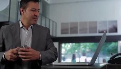 Hispanic businessman typing at laptop then turning to think