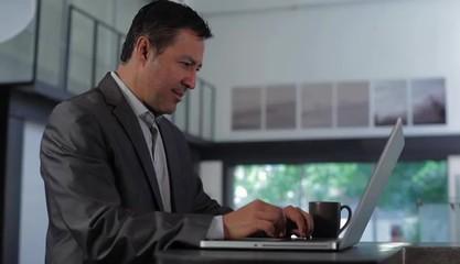 Hispanic businessman typing at laptop then turning to regard camera