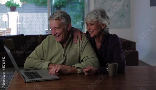 Senior Caucasian couple at home with laptop and credit card