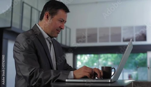 Hispanic businessman typing at laptop then turning to regard camera