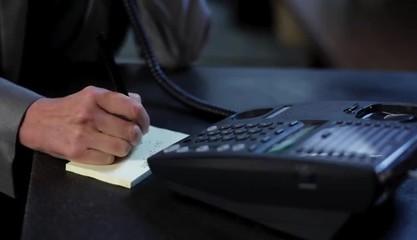 Caucasian businesswoman taking notes, hanging up phone and walking away