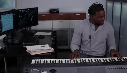 Young man wearing headphones at music station playing electronic keyboard