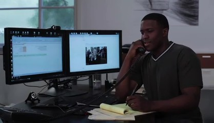 Young man at workstation conversing on telephone