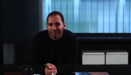 Mature man sitting at desk with digital tablet