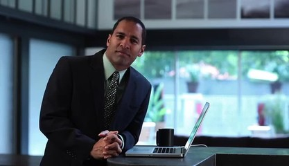 Businessman at counter in creative space with laptop