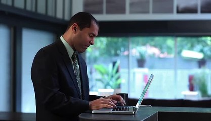 Businessman at counter in creative space typing on laptop