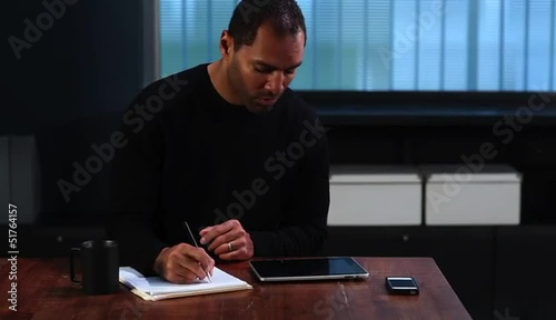 Mature man working with digital tablet and making notes