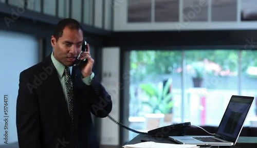 Businessman at counter with laptop conversing on telephone