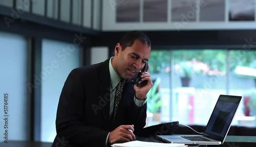 Businessman at counter with laptop talking on telephone and taking notes