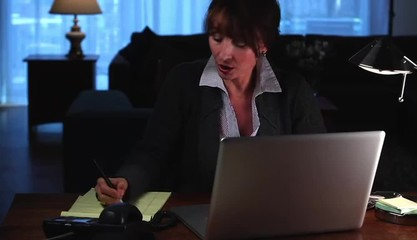 Woman at home using laptop taking notes